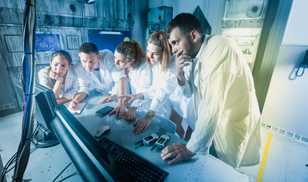Foto de Five positive american adults solving conundrums together in quest room in view as abandoned lab - Imagen libre de derechos