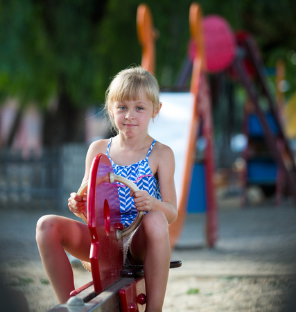 Foto de Little girl having fun on playground playing on swing in summer day - Imagen libre de derechos