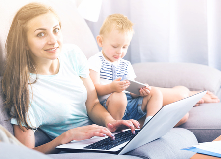 Photo pour Satisfied female is productively working behind laptop while kid playing on tablet at home. - image libre de droit