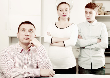 Photo for Pregnant mother and son having disagreement with father at home - Royalty Free Image