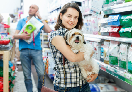 Photo for Young happy  positive smiling woman with dog in pet shop, during shopping with husband - Royalty Free Image