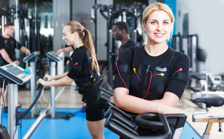 Photo pour Young athletic woman in EMS suit exercising in modern fitness center - image libre de droit
