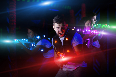 Photo for Emotional guy playing laser tag with friends on dark labyrinth in colorful beams of laser pistols - Royalty Free Image