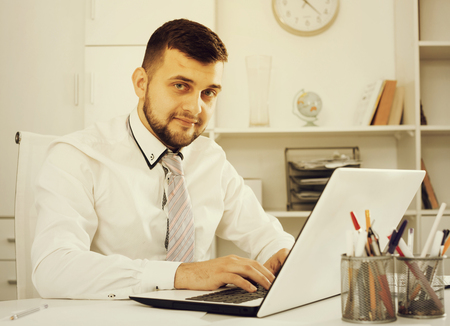 Photo pour Young male worker working productively on project in office - image libre de droit