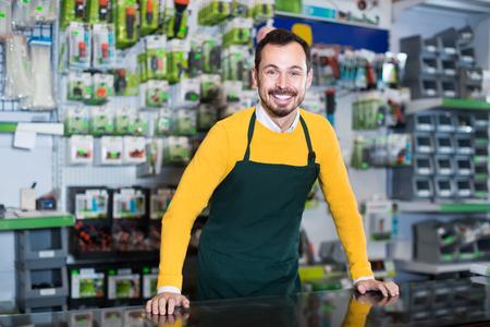 Foto für active male seller showing assortment оf equipment in garden equipment shop - Lizenzfreies Bild