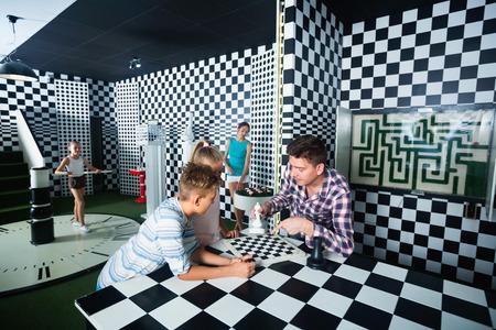 Foto de Happy cheerful  family of five is having fun together in lost chessroom. - Imagen libre de derechos