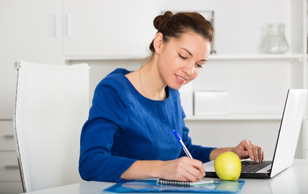 Photo pour Young female worker working productively on project in office - image libre de droit