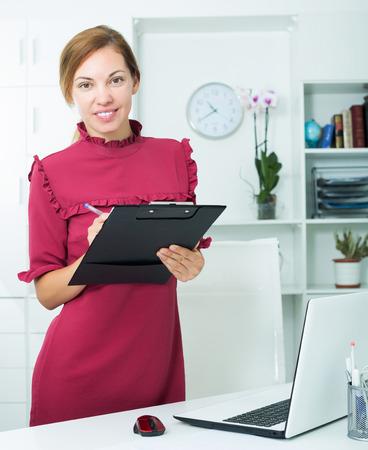 Foto de Smiling woman standing with cardboard in company office indoors - Imagen libre de derechos