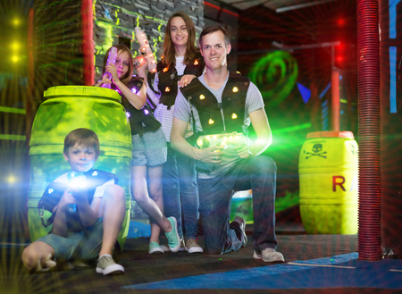 Photo for Modern young parents and children with laser pistols posing together in bright beams in laser tag labyrinth - Royalty Free Image