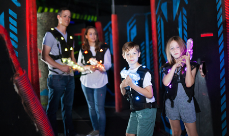 Photo for Happy little brother and sister with laser pistols playing laser tag in dark labyrinth with their parents - Royalty Free Image