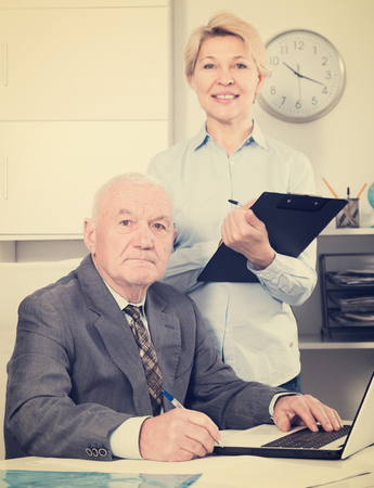 Photo pour Aged manager and secretary working productively together in office - image libre de droit