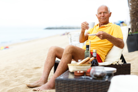 Photo for Great mature man sitting with cup of hot drink on the beach - Royalty Free Image