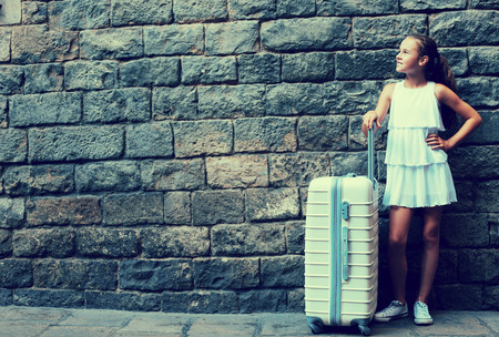 Foto de Smiling girl in white with travelling bag on stone wall background - Imagen libre de derechos