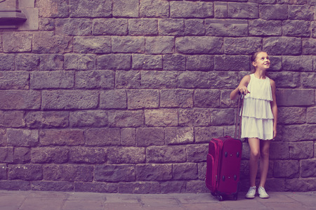 Foto de Happy little girl traveler with suitcase leaning against stone wall of European city - Imagen libre de derechos