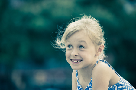 Foto de Closeup happy little girl posing on green city landscape - Imagen libre de derechos