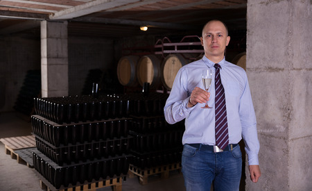 Photo pour Confident winemaker offering glass of white sparkling wine for tasting in wine cellar - image libre de droit