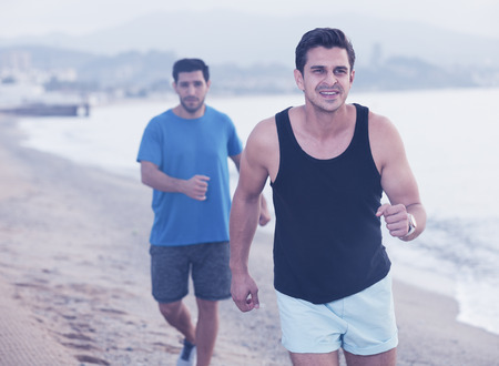 Photo for Two friends are jogging in time training on the beach near sea. - Royalty Free Image
