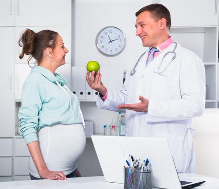 Foto de Middle-aged pregnant visitor consulting smiling man doctor in hospital - Imagen libre de derechos