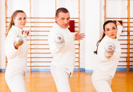 Photo pour Man and women fencers practicing movements together at fencing workout - image libre de droit