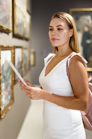 Foto de Intelligent young woman holding brochure with exhibition program near paintings in modern museum - Imagen libre de derechos