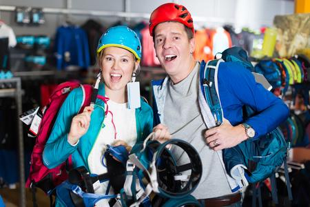 Joyful couple is choosing travel gear in sports shop