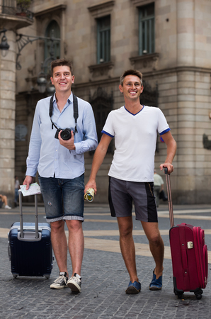 Foto de positive swedish  male couples with travel bags walking the city - Imagen libre de derechos