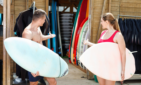 Young happy cheerful positive smiling couple planning to surf, choosing boards and surfing suits in beach club