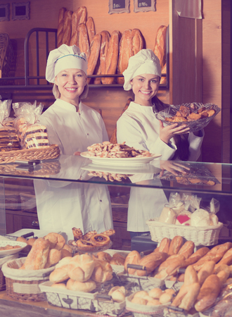 Photo for Bakery commerce staff offering bread and different pastry for sale - Royalty Free Image