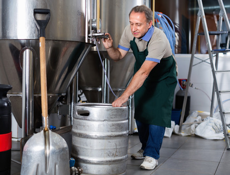 Photo for Portrait of  cheerful positive smiling brewer who is making beer and controls the process in the brew-house. - Royalty Free Image