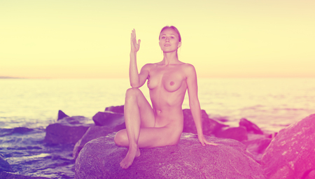 Photo for Nude sporty woman 25-35 years old is sitting on the stone near the sea at the dawn. - Royalty Free Image