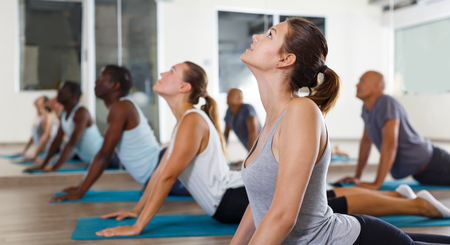 Photo for Nice women and men exercising during yoga class in modern fitness center - Royalty Free Image