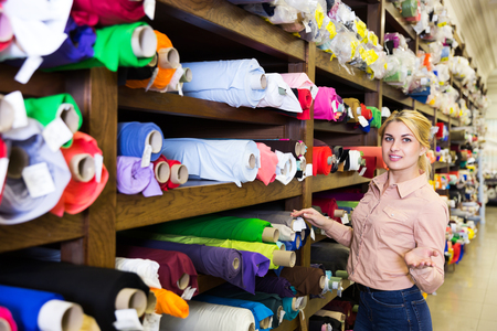 Photo for Portrait of blonde salesgirl working in fabric store, demonstrating wide range of stylish cloth - Royalty Free Image