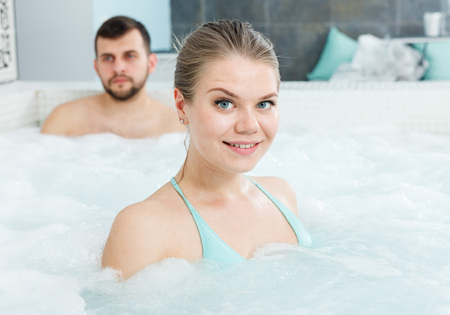 Photo for Young woman relaxing in jacuzzi during wellness weekend in spa center - Royalty Free Image