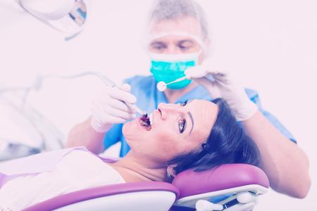 Foto de dentist in uniform health tooth visitor in dentist's chair in the room - Imagen libre de derechos
