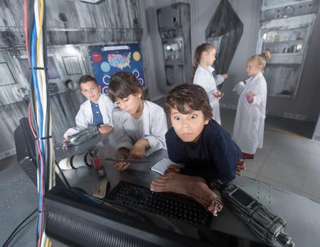 Foto de concentrated schoolkids solve task in the bunker quest room - Imagen libre de derechos