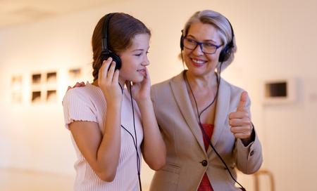Foto de Teenage girl and mature woman using audio guide during excursion in historical museum - Imagen libre de derechos