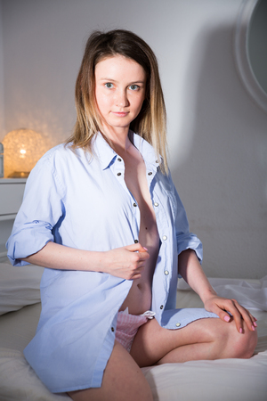 Photo for Cute seductive girl in blue shirt playfully posing in bed  in home interior - Royalty Free Image