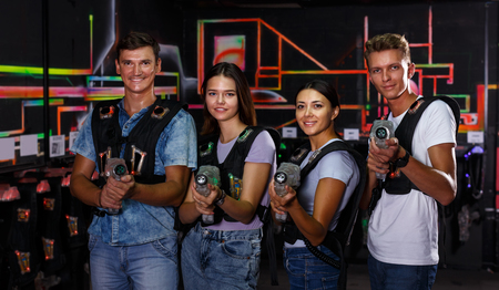Photo for Smiling young people with laser guns having fun together in dark labyrinth - Royalty Free Image