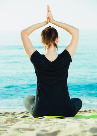 Photo for Female 20-30 years old is sitting her back and practicing meditation in black T-shirt on the beach. - Royalty Free Image