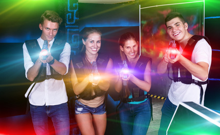 Photo for Four cheerful young guys an girls posing with laser pistols in their hands in dark laser tag room - Royalty Free Image