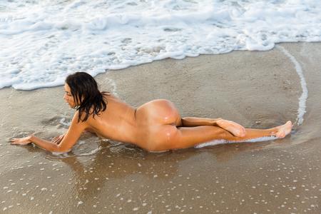 Foto de Back view  of nudity sexy girl playfully posing with  on the sandy beach - Imagen libre de derechos