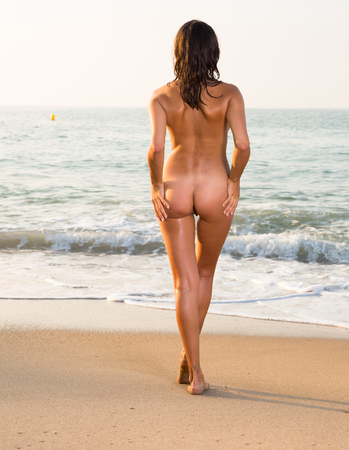 Photo pour Nude slender girl standing back to viewer on beach against azure sea - image libre de droit