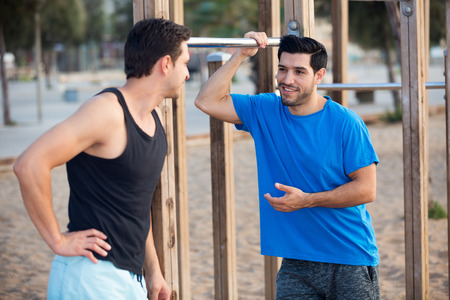 Photo for Smiling adult men are talking in time warming-up in the park near beach. - Royalty Free Image