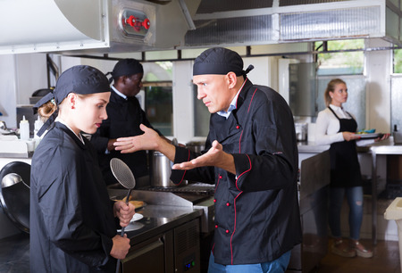 Photo for Exasperated head chef scolding upset female employee in kitchen of restaurant - Royalty Free Image