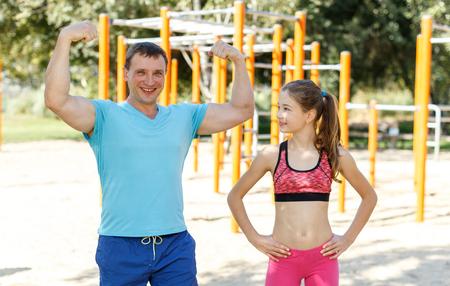 Foto de Portrait of happy athletic man and his slim preteen daughter during workout outdoors - Imagen libre de derechos