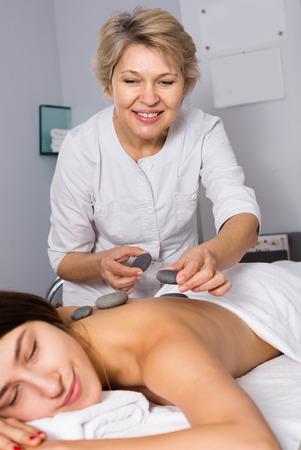Foto de Young smiling woman having professional massage in spa salon - Imagen libre de derechos
