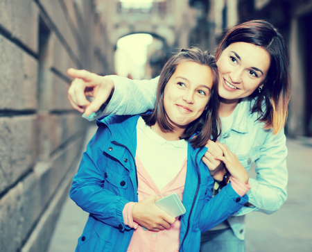 Foto de Smiling mother and daughter looking at sight during sightseeing tour - Imagen libre de derechos