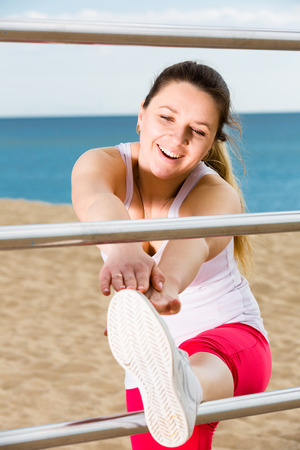 Photo for Young smiling woman doing exercises on beach by ocean at daytime - Royalty Free Image