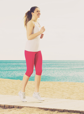 Photo for Young fit woman running on beach in sunny morning - Royalty Free Image