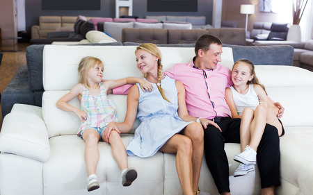 Photo pour Man and woman with kids is pleased by new sofa in furniture store - image libre de droit